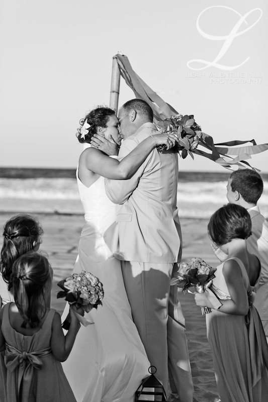 black and white of first kiss at a wedding ceremony on the beach in nags head, nc