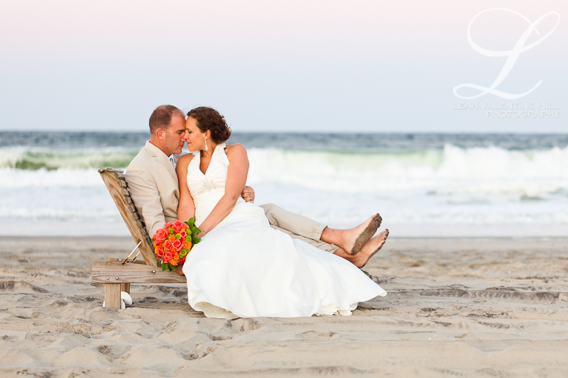 portrait of bride and groom on wooden chase lounge on the beach in nags head, nc