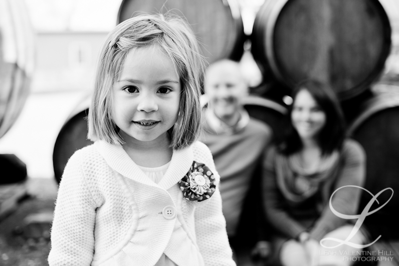 portrait of a girl with her parents in the background leaning on wine barrels at a winery in charlottesville, va