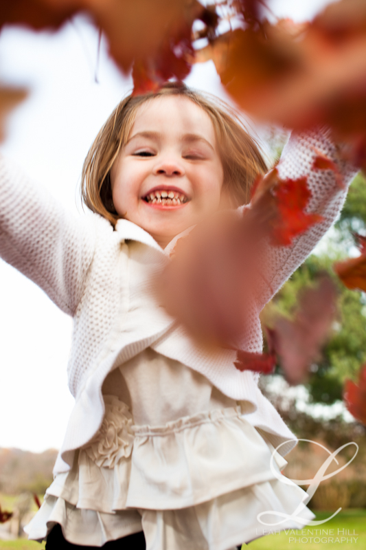 portrait of a girl throwing leaves