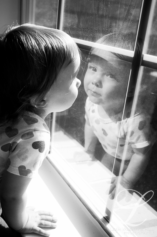 reflection portrait of a toddler looking in the window