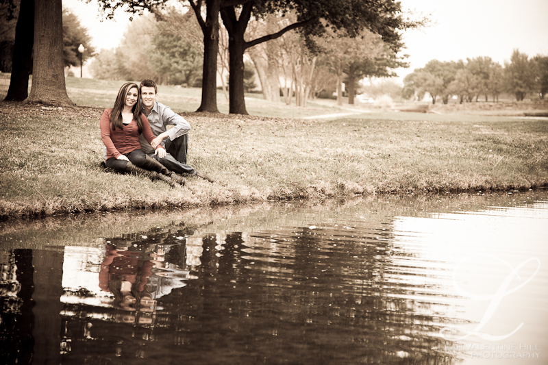 antique processed engagement portrait sitting by a pond giving their reflection in dallas, tx