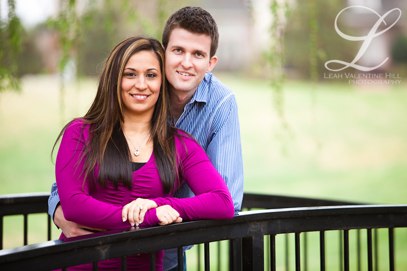engagement portraits on a small bridge with a weeping willow in the background in dallas, tx