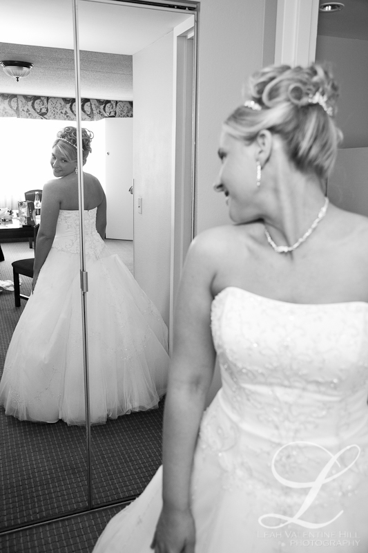 black and white portrait of a bride looking at herself in the mirror