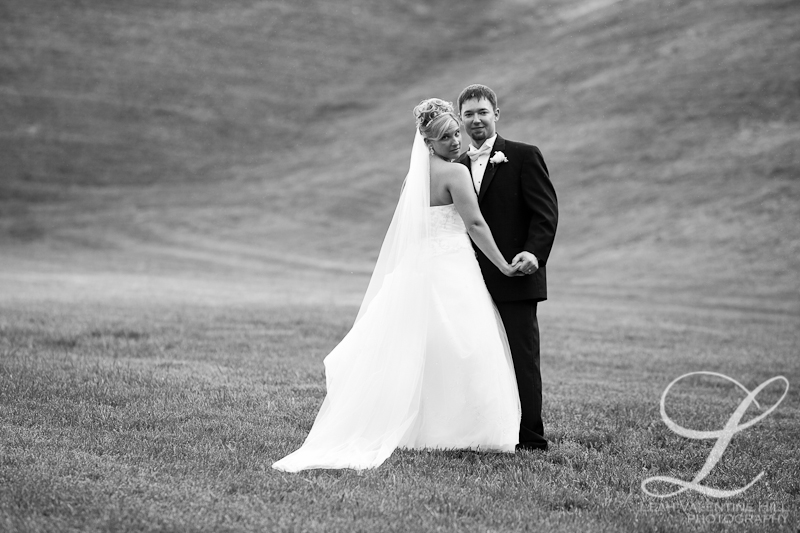 black and white portrait of bride and groom in an empty field at the doubletree hotel in charlottesville va