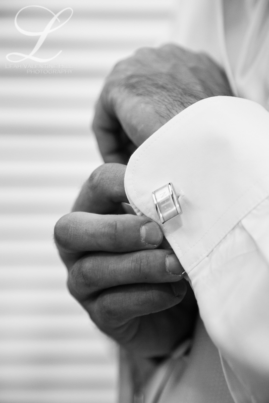 black and white photo of groom putting on his cufflinks