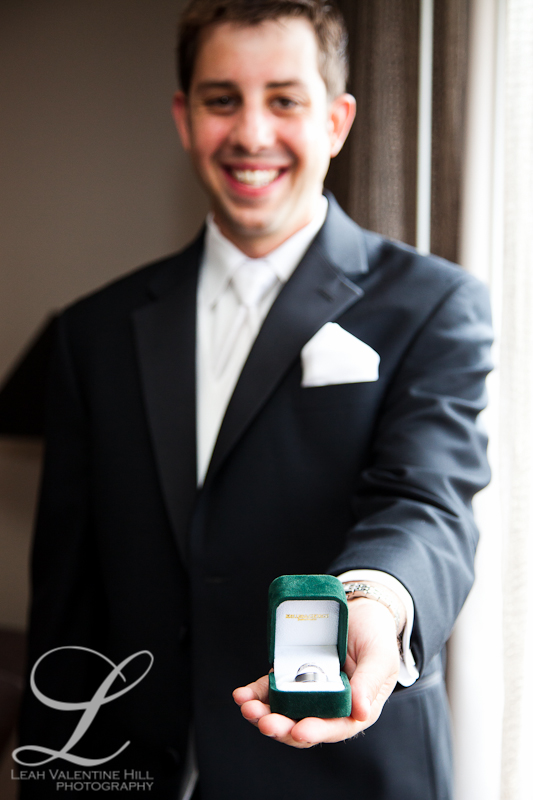 groom holding the wedding rings at the omni hotel in charlottesville va