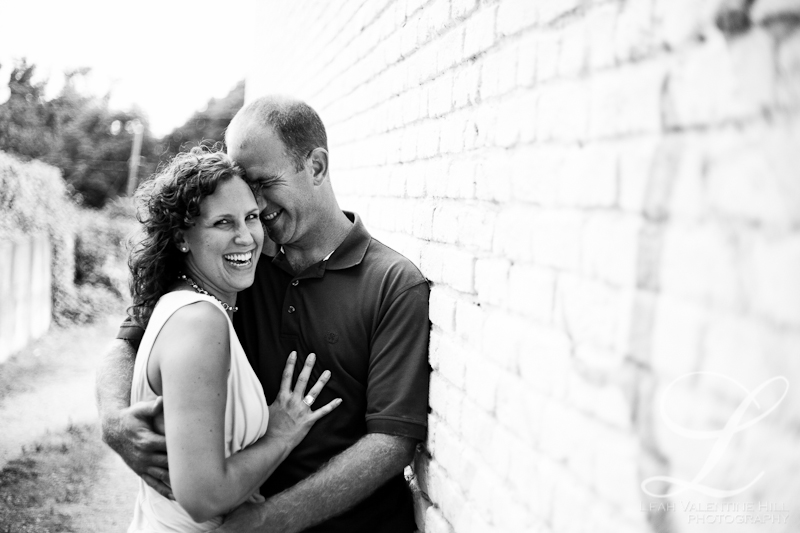 black and white engagement portrait along a white brick wall in charlottesville, va