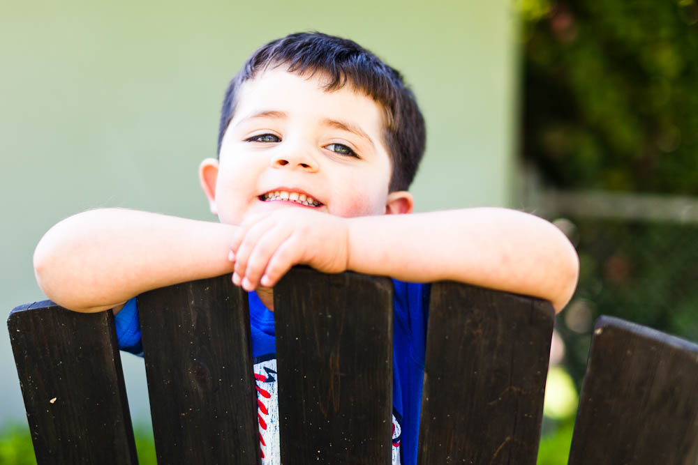 portrait of young boy on a wooden chair in santa ana, ca