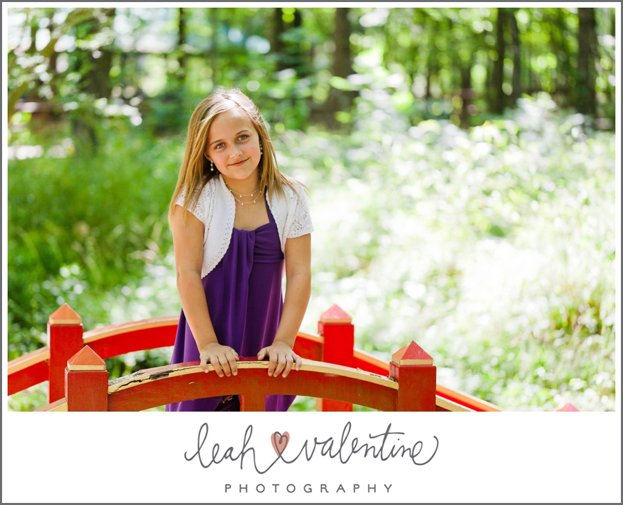 portrait of a girl standing on a red bridge at wildwood park in west little rock, ar