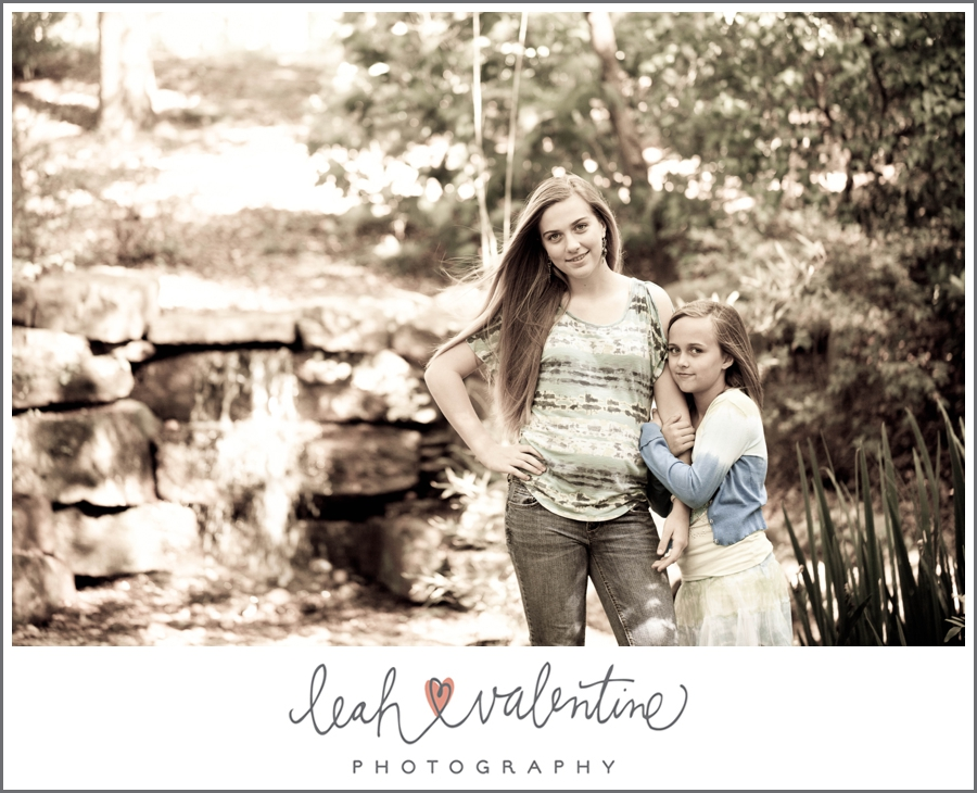 portrait of big sister and little sister near a waterfall in wildwood park west little rock, ar