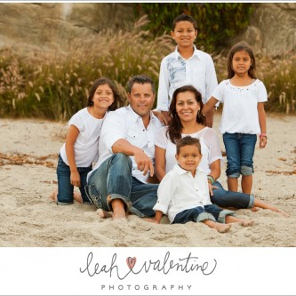 family portraits sitting in the sand on Aliso Beach in Laguna Beach, CA