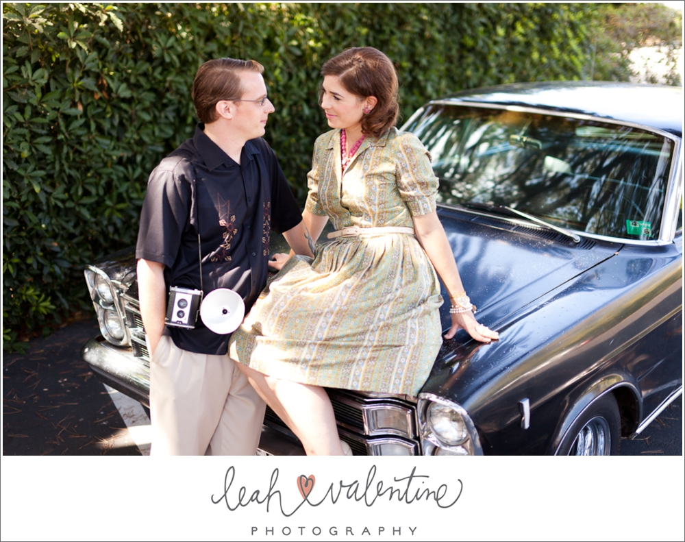 1960s styled engagement portraits on a vintage car with a vintage camera in santa barbara ca