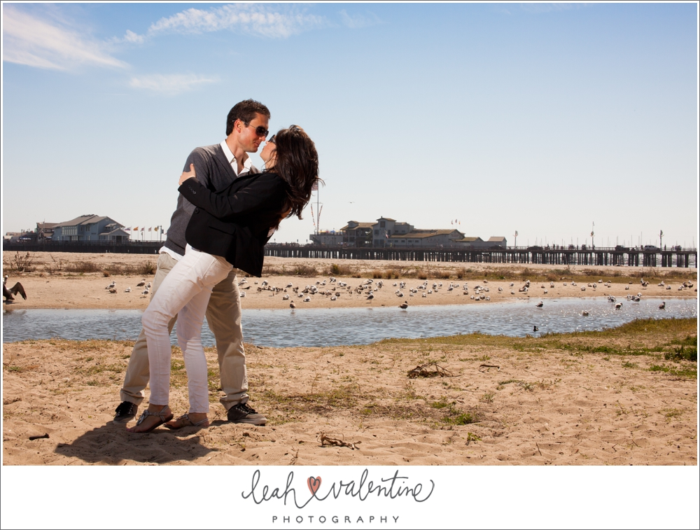 portrait of couple on the beach with sterns warf in the background in santa barbara