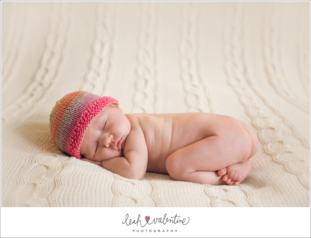santa barbara newborn portrait on a beige blanket with pink beanie hat